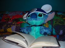 Stitch reading a book