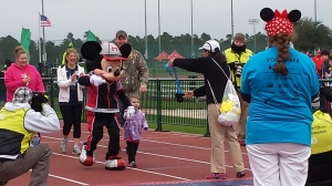 Mickey in a track suit, holding hands with a small kid and heading to finish line